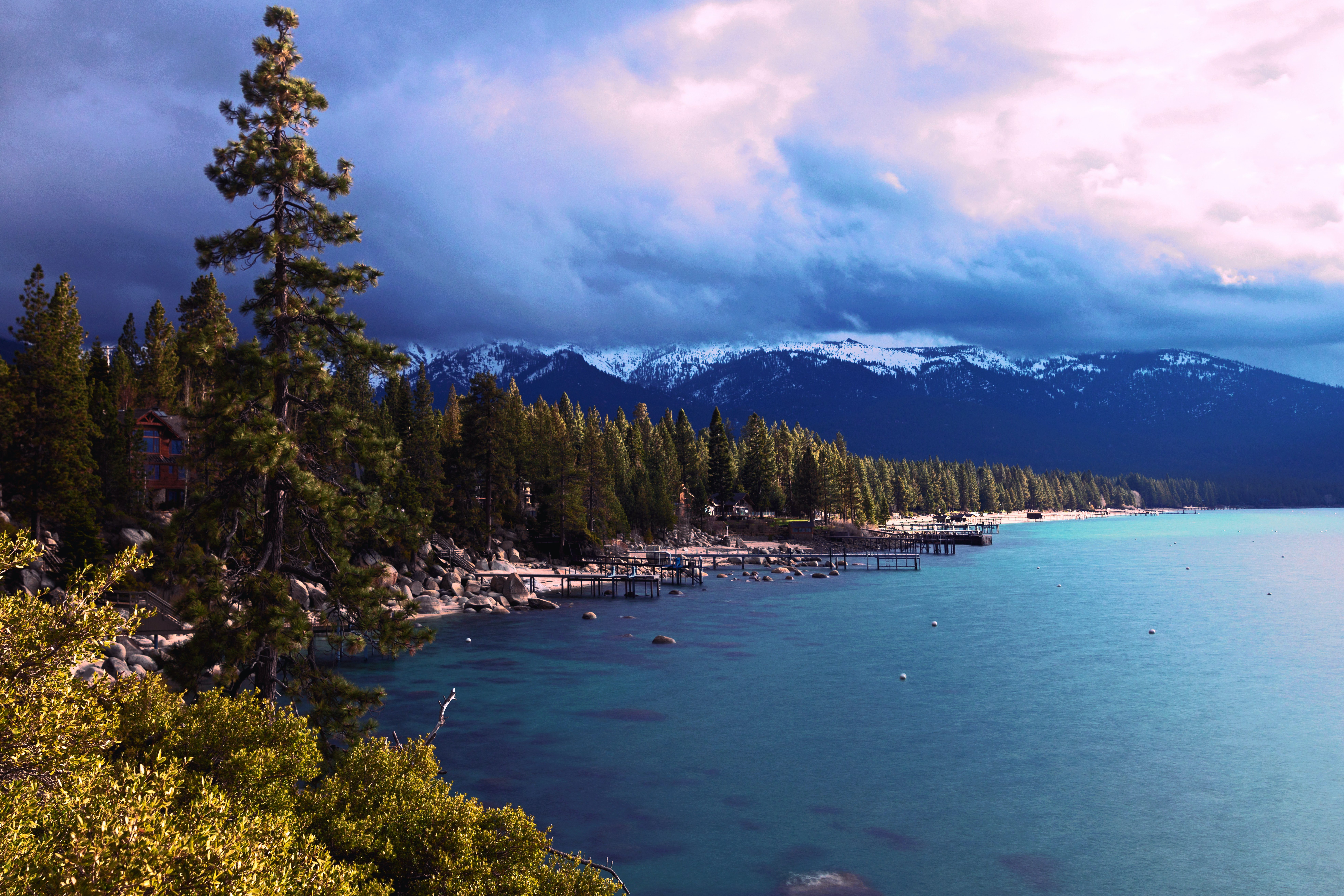 Photo of Lake Tahoe with snow-capped mountains and piers lining the lake